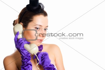 woman in corset and little hat talking on the phone