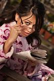 Pretty Hispanic Woman in Bathrobe with Newspaper