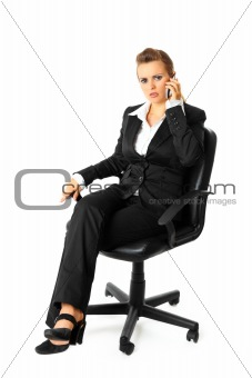Thoughtful modern business woman sitting on chair and talking on mobile phone