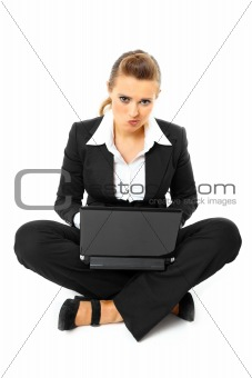 Laying on floor thoughtful modern business woman using  laptop
