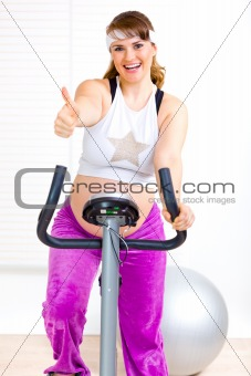 Smiling beautiful pregnant woman working out on static bicycle and showing thumbs up gesture