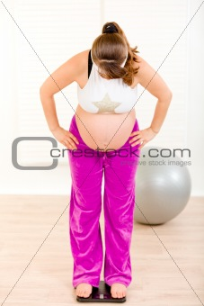 Pregnant woman standing on weight scale at home