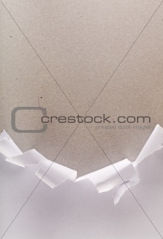 Torn wrapping paper revealing cardboard box