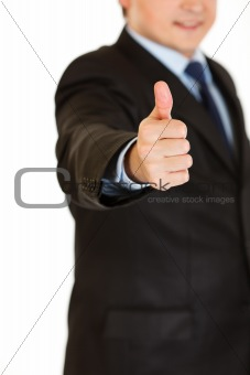 Smiling businessman showing  thumbs up gesture.   Close-up.