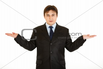 Friendly young  businessman presenting something on empty hands