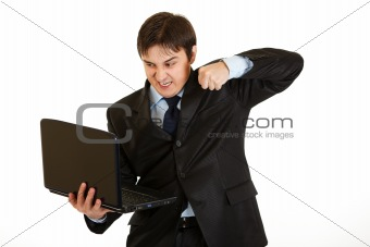 Angry young businessman trying to hit laptop