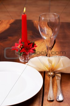 Beautiful table setting with a candle in the background