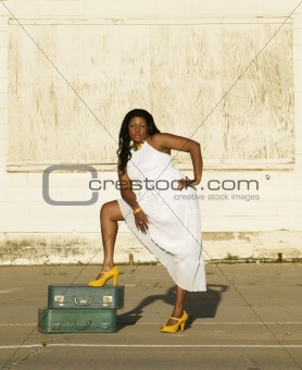 African American woman with foot on suitcases