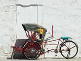 Trishaw parked at a white wall