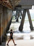 Woman walking on shore under walkway pillars