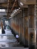 Woman running on shore under pillared walkway