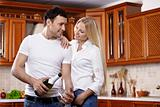 Couple with champagne on kitchen