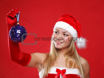 A young girl dressed as Santa Claus on a red background holds a New Year's toy