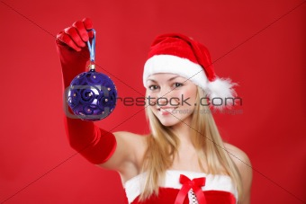 A young girl dressed as Santa Claus on a red background holds a