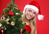 The young beautiful girl dressed as Santa and a christmas fur-tree