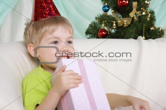 Little boy near to christmas fur-tree sits with gift