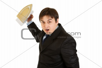 Angry modern businessman menacingly holding iron in hand
