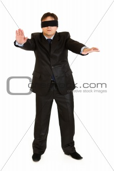 Disoriented businessman with blindfold covering his eyes