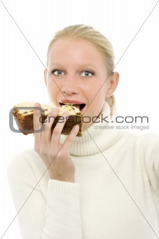 portrait of a young caucasian woman wearing a white turtleneck sweater and holding a slice of panettone