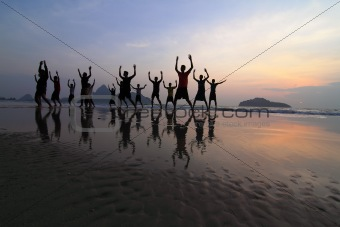 group of happy young people silhouettes jumping on the beach on