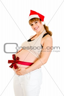Happy beautiful pregnant woman in Santa hat with  red ribbon on belly