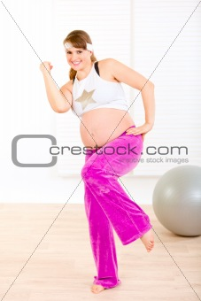 Smiling beautiful pregnant woman doing fitness exercises at home