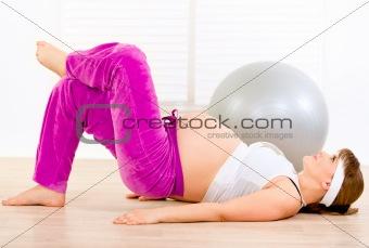 Smiling beautiful pregnant female making gymnastics at living room