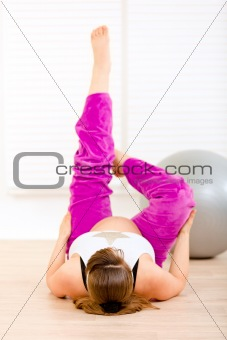 Smiling beautiful pregnant female making gymnastics at living room