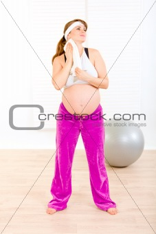 Beautiful pregnant female wiping her face with towel after exercising at home