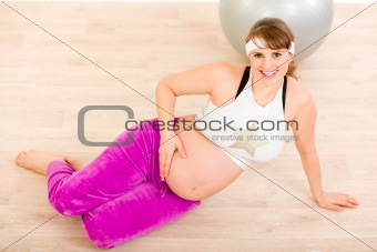 Smiling beautiful pregnant female sitting on floor and relaxing after exercising