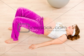 Smiling beautiful pregnant female doing fitness exercises at home