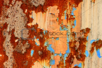 A rotted metal panel covered in rust