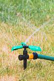 Close up of lawn sprinkler in summer day