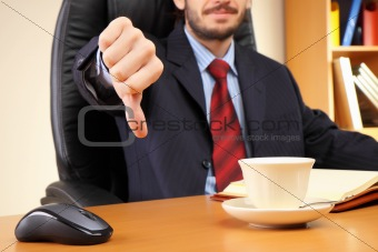 Businessman at his workplace shows thumb down.