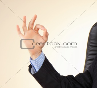 Business man at his workplace shows gesture by fingers.