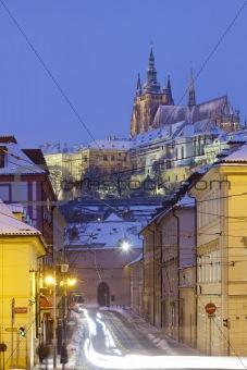 prague in winter - hradcany castle and traffic at mala strana  at dusk