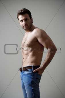 young shirtless musculous man in jeans looking - isolated on gray