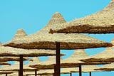 Umbrellas on blue sky background