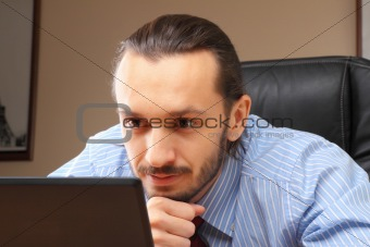 Businessman at his workplace look in laptop.