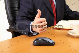 Businessman at his workplace hold thumbs up.