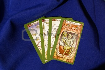 Four tarot cards on blue textile  background
