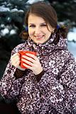 Happy young woman drinking hot tea