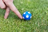 Man hand playing role of soccer player with small blue ball