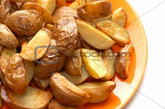 Potatoes baked in their jackets on orange plate