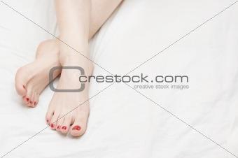 Beautiful adult woman legs on white bedsheet