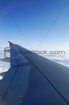 Aircraft wing. High-altitude flight on blue skies.