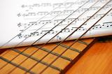 Musician notes under spanish guitar's strings