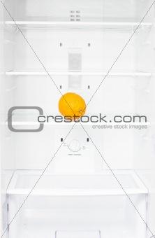 One orange in empty white fridge