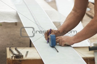 Construction activity: worker drawing line on plastic panel