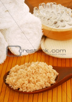 bath salt on a wooden spoon with bath accessories